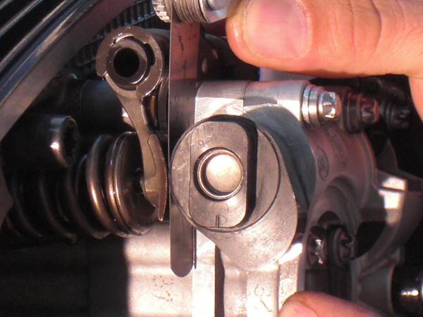 The valve clearance is easily checked between the cam and rocker arm.
